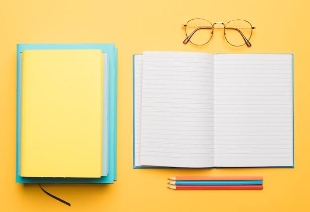 Caderno aberto e pilha de livros ao lado de óculos e conjunto de lápis