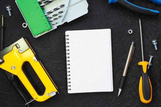 Caderno aberto e várias ferramentas para reparo e construção em um fundo preto estrutural. copie o espaço.