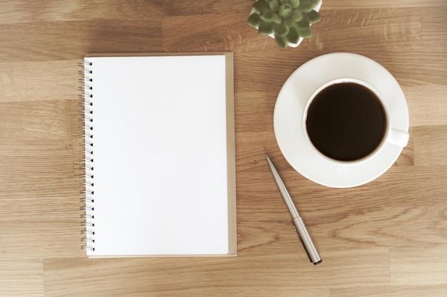 Caderno aberto em branco ao lado da xícara de café na mesa de madeira com espaço de cópia