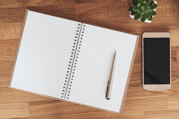 Caderno aberto em branco ao lado de smartphone e xícara de café na mesa de madeira