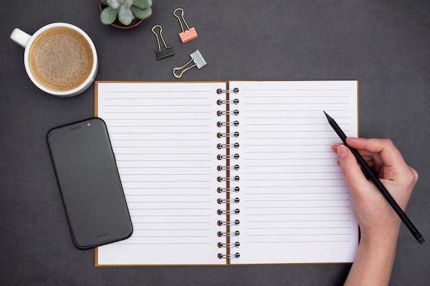 Caderno aberto em branco com página vazia, xícara de café e mão segurando um lápis. tampo da mesa, ondark do espaço de trabalho, fundo preto textured. lay criativo apartamento.