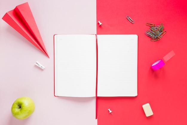 Caderno aberto em branco com vários itens de papelaria