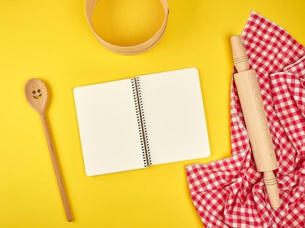 Caderno aberto em branco e acessórios de cozinha de madeira