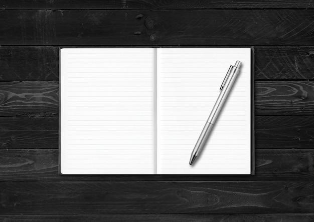 Caderno aberto em branco e maquete de caneta isolada em madeira preta