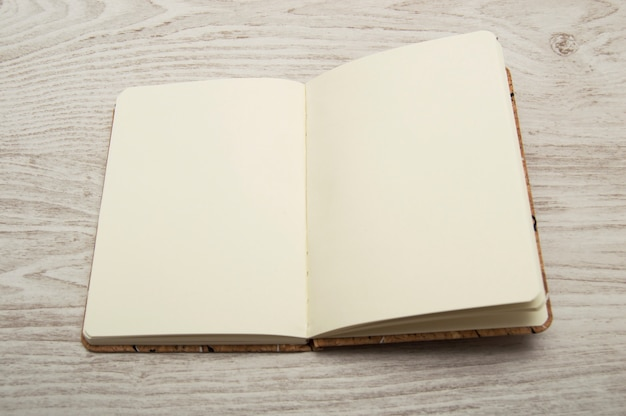 Caderno aberto, em branco, na mesa de madeira.