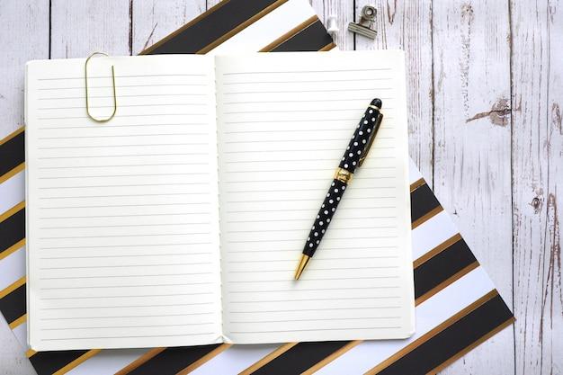 Caderno aberto em linha, um clipe e uma caneta em uma mesa de madeira.