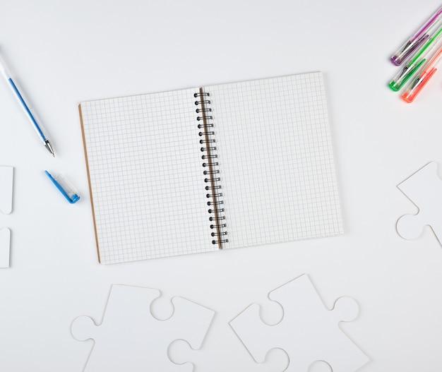 Caderno aberto em uma célula e sobre um fundo branco