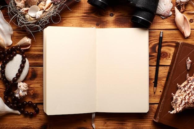 Caderno aberto em uma página em branco, cercada por conchas do mar e muitos outros objetos: livro antigo, binóculos, caixa de madeira, chapelim, pedras e lápis.