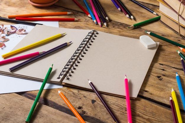 Caderno aberto, folha de papel puro, lápis de cor sobre a mesa de madeira velha