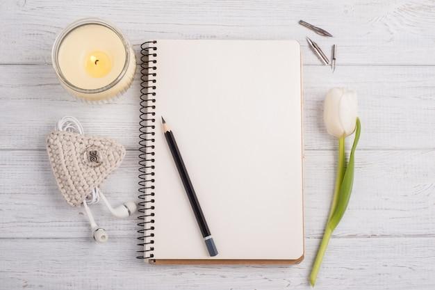 Caderno aberto, lápis, vela, earpods e tulipa