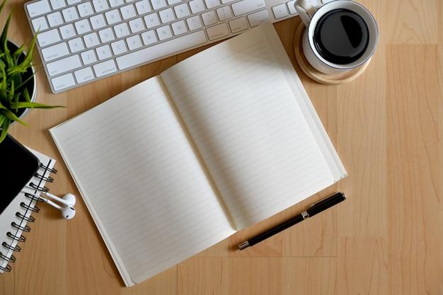 Caderno aberto no desktop de madeira de escritório com material de escritório