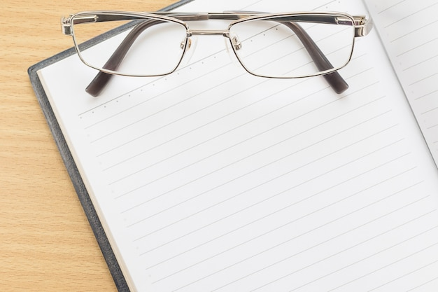 Caderno aberto página em branco e óculos
