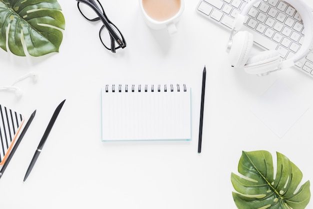 Caderno aberto perto de artigos de papelaria e dispositivos eletrônicos