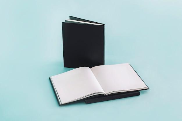 Caderno aberto perto de blocos de notas com capa preta