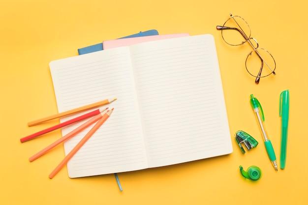 Caderno aberto perto de material escolar e óculos