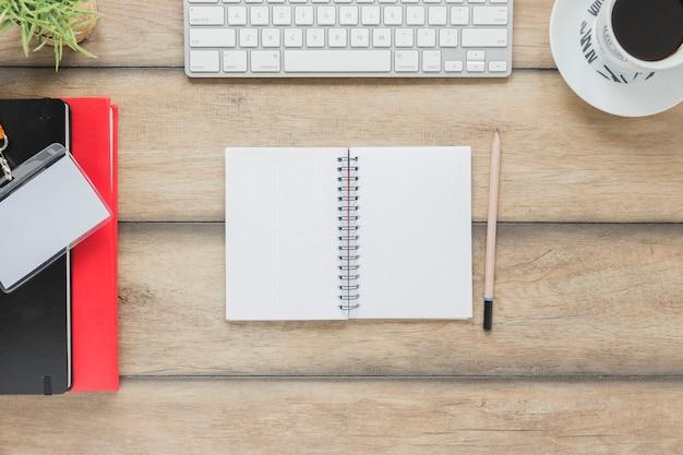Caderno aberto perto de teclado de papelaria e xícara de café