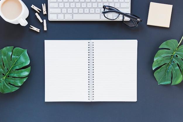 Caderno aberto perto de teclado e xícara de café na mesa com folhas e óculos
