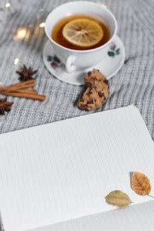 Caderno aberto perto de xícara de chá