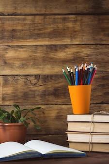 Caderno aberto, pilha de livros, lápis de cor em um copo de plástico e flor em uma panela sobre um fundo de madeira