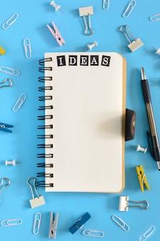 Caderno aberto sobre um fundo azul claro com a palavra ideias