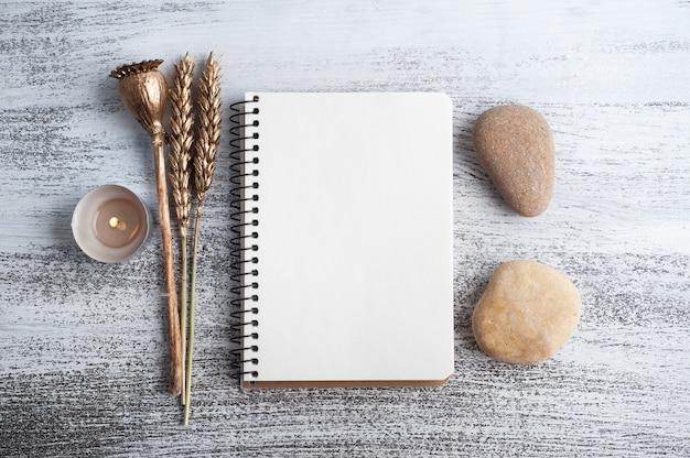 Caderno aberto vazio e flores douradas secas em fundo rústico. cartão com espaço de cópia para o seu texto