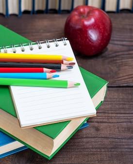 Caderno aberto vazio e lápis de madeira multicoloridos
