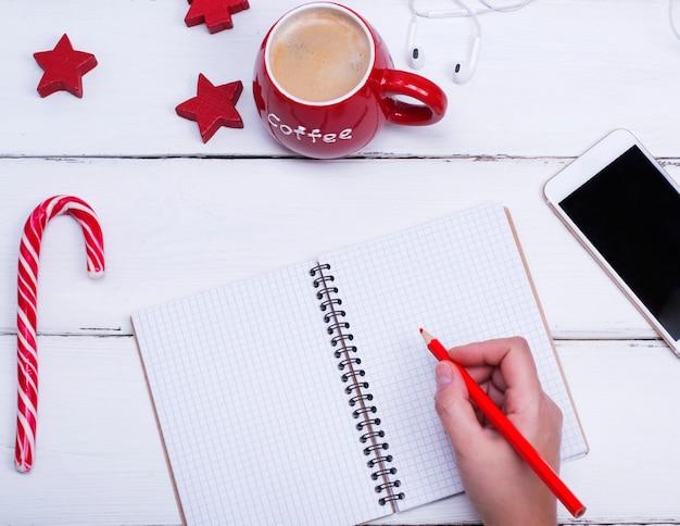 Caderno aberto vazio e mão feminina com um lápis de madeira vermelho