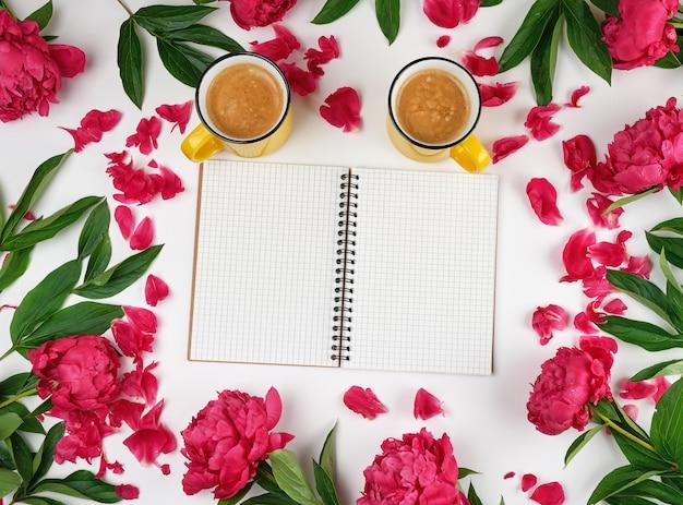 Caderno aberto vazio em uma gaiola e duas xícaras de café amarelas