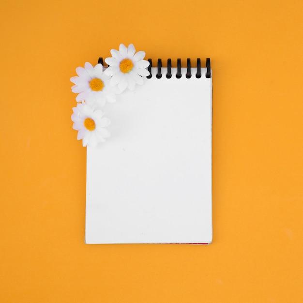 Caderno amarelo com flores silvestres