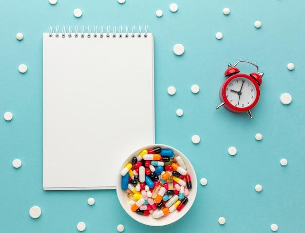 Caderno ao lado de comprimidos e relógio