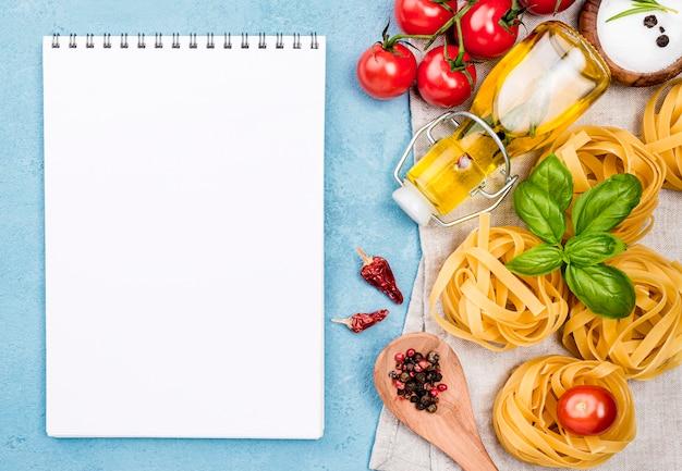 Caderno ao lado de macarrão com legumes