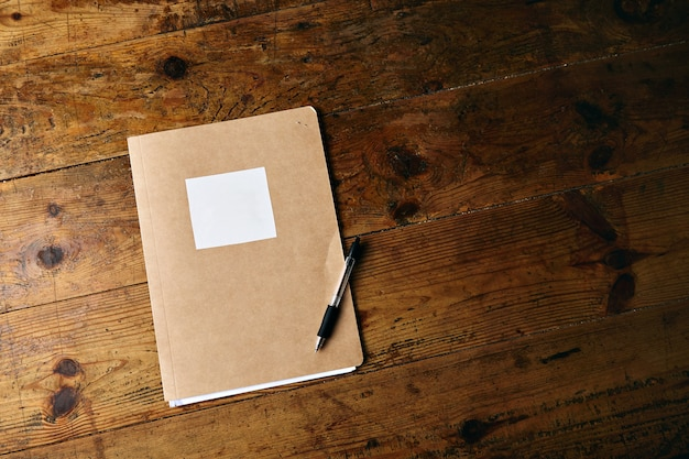 Caderno artesanal sem etiqueta e uma caneta de plástico preta em uma velha mesa de madeira texturizada