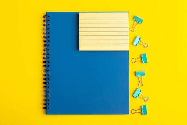 Caderno azul aberto de vista frontal na mesa amarela