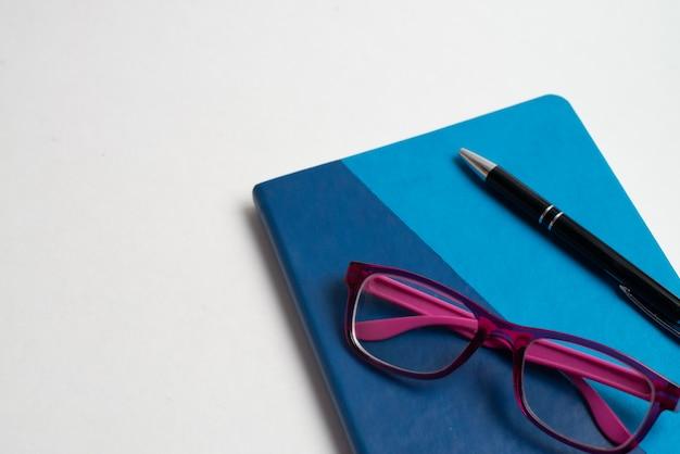 Caderno azul com óculos e caneta preta