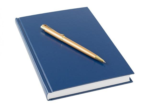 Caderno azul com uma caneta de ouro isolada no fundo branco.