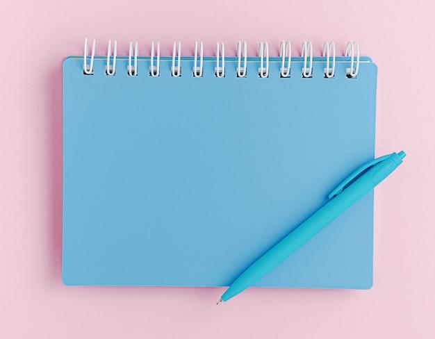 Caderno azul fechado e caneta no espaço rosa. vista superior, maquete.