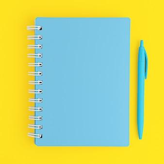 Caderno azul fechado e caneta sobre fundo amarelo. vista superior, maquete.