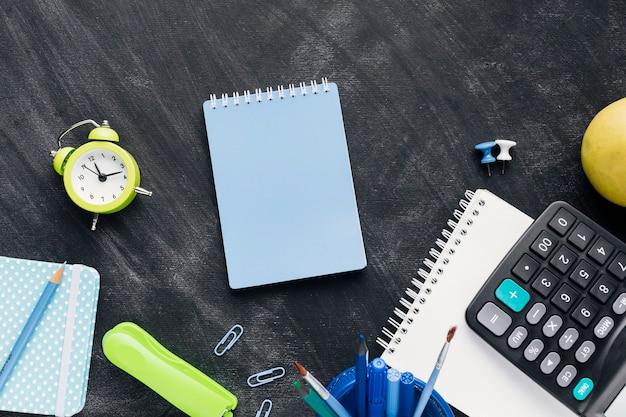 Caderno azul perto de escritório implementa no quadro-negro
