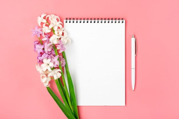 Caderno branco aberto, caneta, buquê de flores jacintos em fundo rosa