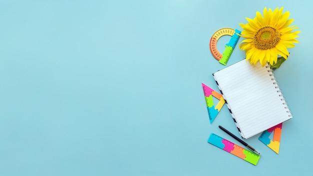 Caderno branco aberto da escola e girassol no fundo azul