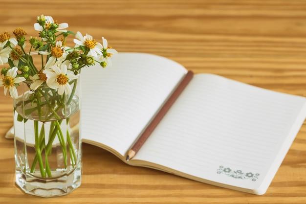 Caderno branco aberto na tabela de madeira rústica com lápis marrom ou preto.