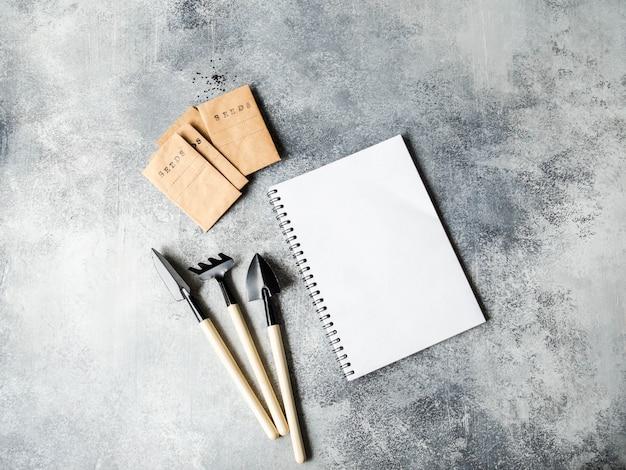 Caderno branco aberto para texto, ferramentas de jardim e sementes em sacos de papel