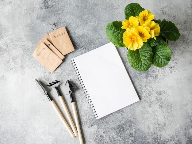Caderno branco aberto para texto, flor de prímula amarela, ferramentas de jardim e sementes em sacos de papel
