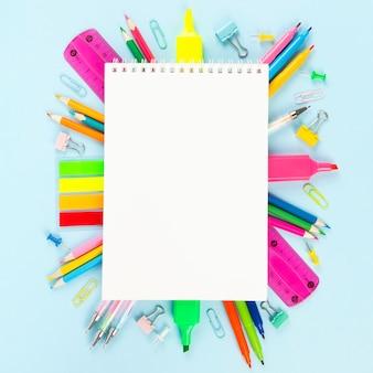 Caderno branco cercado por várias fontes da secretaria da escola e da pintura no fundo azul. volta ao conceito de escola. vista do topo. copie o espaço