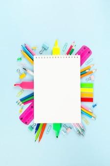 Caderno branco cercado por vários materiais de escritório escolar