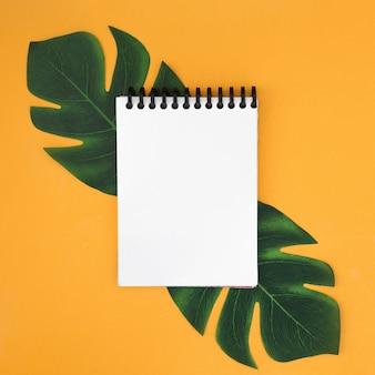 Caderno branco com folhas tropicais