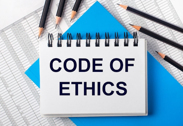 Caderno branco com o texto código de ética na mesa ao lado de lápis preto sobre fundo azul e relatórios. conceito de negócios