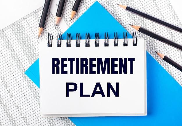 Caderno branco com o texto plano de aposentadoria na mesa ao lado de lápis preto sobre fundo azul e relatórios. conceito de negócios