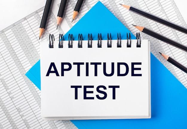 Caderno branco com o texto teste de aptidão na mesa ao lado de lápis preto sobre fundo azul e relatórios. conceito de negócios