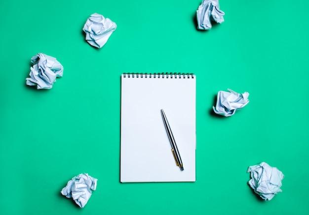 Caderno branco com pena em um fundo verde entre as bolas de papel. o conceito de gerar